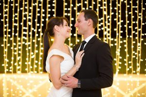 'Couple in front of fairy light curtain'